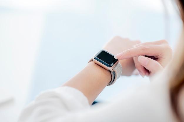 Vue rapprochée de la femme à l'aide de l'application smartwatch, copiez l'espace.