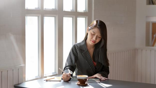 Vue rapprochée de la femme à l'aide d'une tablette numérique avec stylet dans un lieu de travail moderne sombre