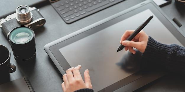 Vue rapprochée de la femme designer s'appuyant sur une tablette dans un lieu de travail élégant et sombre