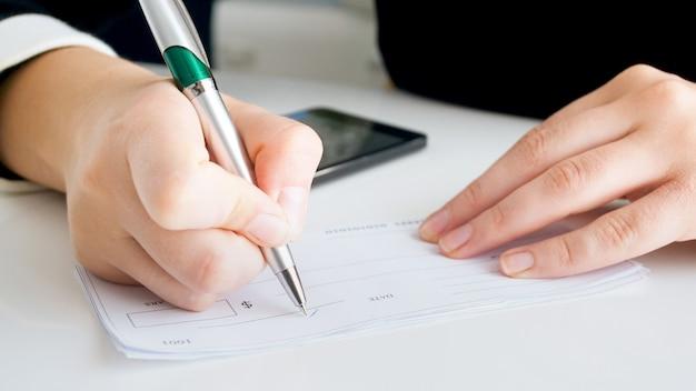 Vue rapprochée d'une femme écrivant une signature sur un chèque bancaire.