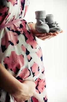 Vue rapprochée d'une femme enceinte en robe imprimée florale tenant de petites chaussures tricotées pour bébés