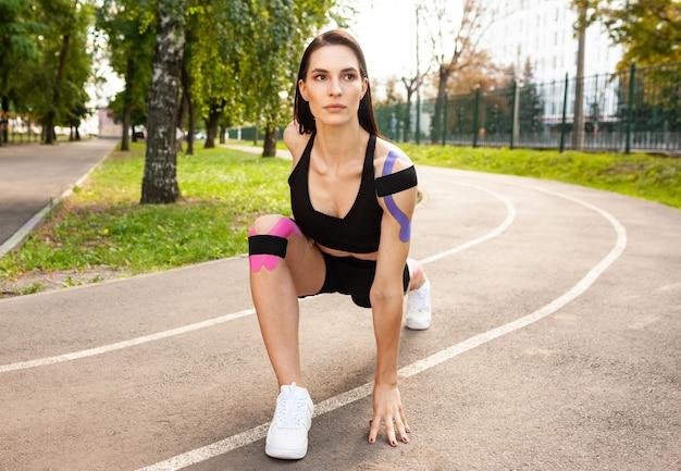 Vue rapprochée de la femme flexible bruette avec corps musclé se réchauffant à l'extérieur, pratiquant des fentes profondes.