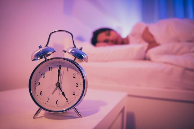Vue rapprochée de la femme de l'horloge de signal de cloche couchée dans son lit
