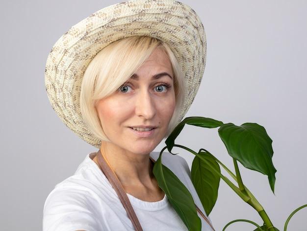Vue rapprochée d'une femme jardinière blonde d'âge moyen en uniforme portant un chapeau