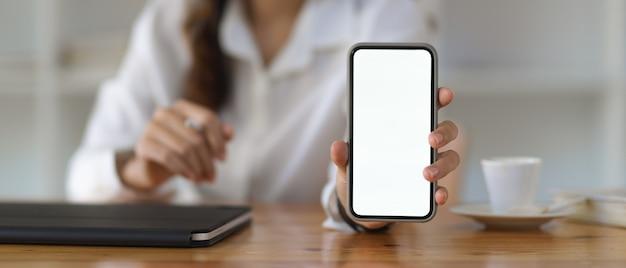 Vue rapprochée de la femme montrant l'écran du smartphone comprennent un tracé de détourage