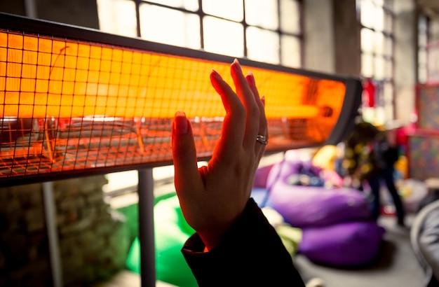 Vue rapprochée d'une femme se réchauffant les mains au radiateur infrarouge