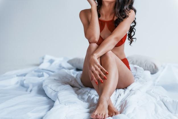 Vue rapprochée d'une femme en sous-vêtements rouges assis sur un lit blanc.