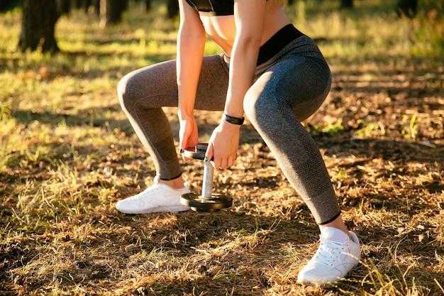 Vue rapprochée de la femme sportive, soulever un haltère, tout en exerçant dans le parc.