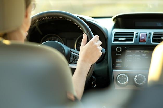 Vue rapprochée d'une femme tenant un volant au volant d'une voiture dans la rue par une journée ensoleillée.
