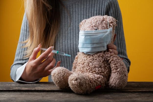 Vue rapprochée d'une femme vaccinant un ours en peluche dans une image conceptuelle de soins pédiatriques.