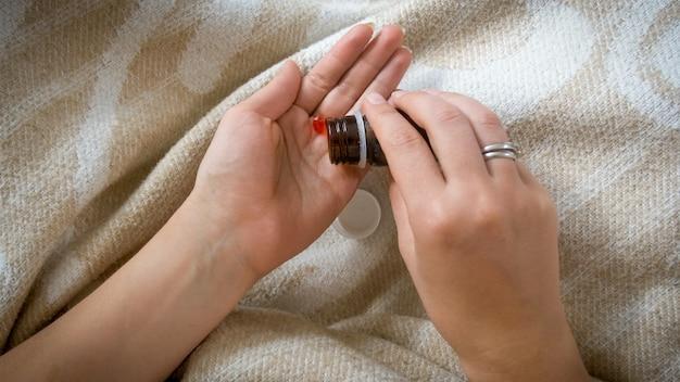 Vue rapprochée d'une femme versant des pilules ou des comprimés à portée de main à partir d'une bouteille en verre