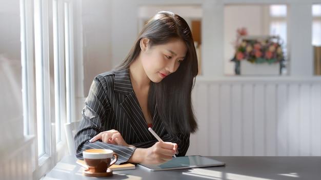 Vue rapprochée des femmes d'affaires travaillant sur une tablette numérique en milieu de travail moderne