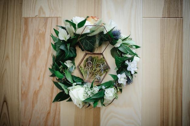 Vue rapprochée de fleurs blanches, anneaux de mariage dans une boîte rustique avec des plantes à l'intérieur
