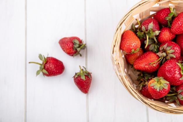 Vue rapprochée des fraises dans le panier et sur la surface en bois