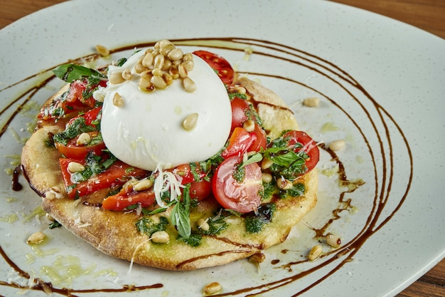 Vue rapprochée sur le fromage burrata italien avec sauce focaccio, tomates, basilic et noix. plat de restaurant sur une table en bois. vue rapprochée. mise à plat de nourriture