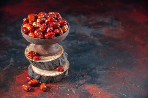 Vue rapprochée de fruits crus à l'intérieur et à l'extérieur d'un bol sur des planches de bois sur le côté droit sur fond de couleurs mélangées