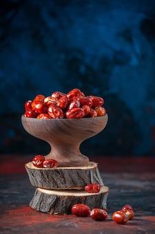 Vue rapprochée des fruits crus à l'intérieur et à l'extérieur d'un bol sur des planches de bois sur fond de couleurs mélangées