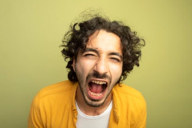Vue rapprochée de furieux jeune bel homme caucasien regardant la caméra crier isolé sur fond vert olive