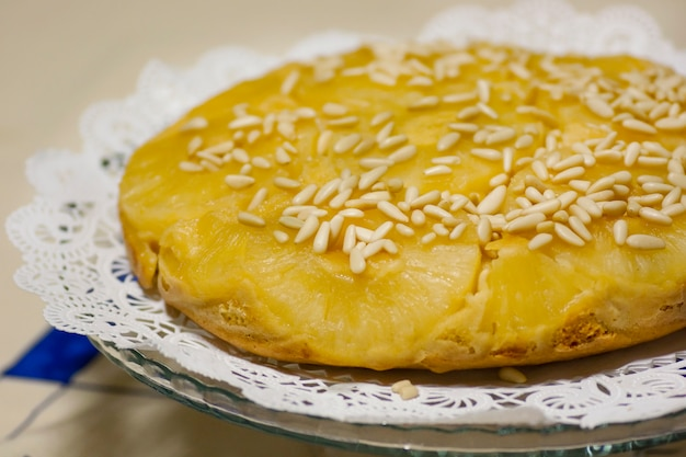 Vue rapprochée d'un gâteau à l'ananas homemage décoré de pignons de pin.