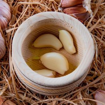 Vue rapprochée de gousses d'ail pelées dans un broyeur d'ail sur fond de paille