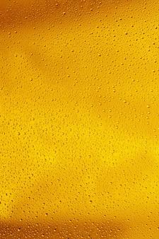 Vue rapprochée de gouttes froides sur le verre de fond de bière. texture de boisson alcoolisée rafraîchissante avec des macro-bulles sur le mur de verre. fizzing ou flottant jusqu'au sommet de la surface. de couleur dorée.