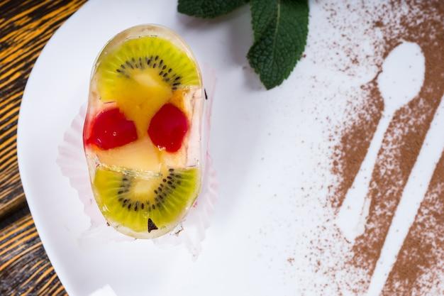 Vue rapprochée en grand angle d'un dessert aux fruits individuel garni de kiwi et de cerises - disposé pour ressembler à un visage souriant - garni de menthe et servi sur une assiette blanche avec saupoudrage de cacao
