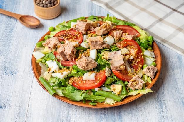 Vue rapprochée sur une grande assiette avec une salade savoureuse: tomate, fromage feta, thon, asperges et légumes verts. fond de photo de nourriture. salade saine, amaigrissante et équilibrée