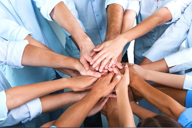 Vue rapprochée d'un groupe de personnes empilant les mains