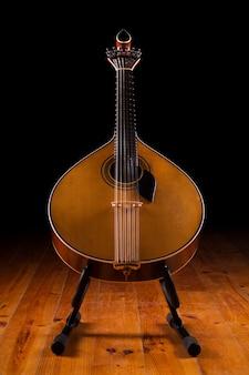Vue rapprochée d'une guitare portugaise traditionnelle sur un fond sombre.