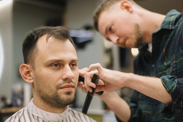 Vue rapprochée de hairstilyst donnant une coupe de cheveux