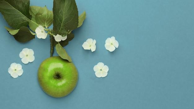 Une vue rapprochée d'en haut d'une pomme verte entourée de fleurs blanches sur fond bleu