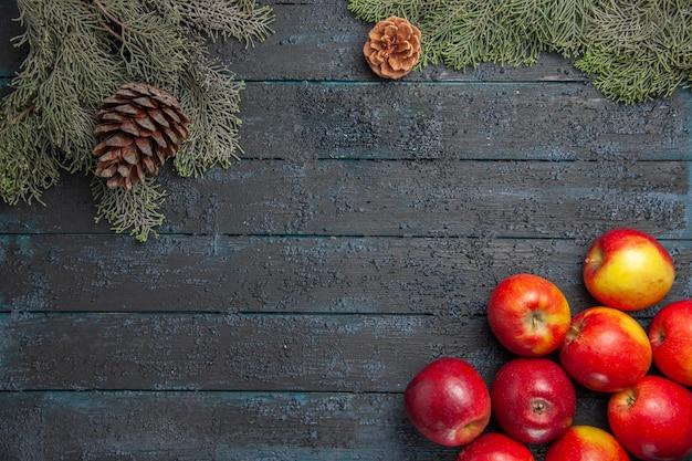 Vue rapprochée en haut des pommes sur une table grise de nombreuses pommes en bas à droite et des branches d'arbres avec des cônes