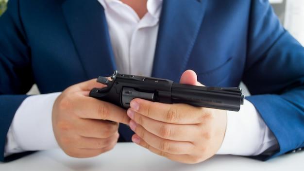 Vue rapprochée d'un homme d'affaires tenant un pistolet alors qu'il était assis au bureau