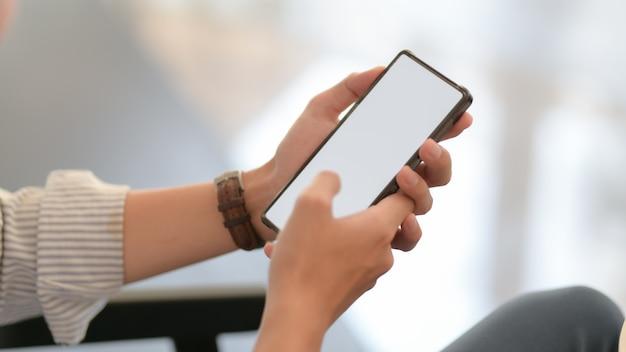 Vue rapprochée de l'homme d'affaires textos sur smartphone tout en étant assis sur le canapé