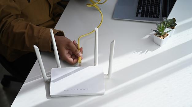 Vue rapprochée de l'homme branchant le câble au routeur sans fil. internet sans fil.