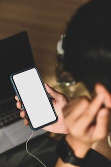 Vue rapprochée d'un homme écoutant de la musique sur un smartphone tout en faisant de l'exercice dans le salon.
