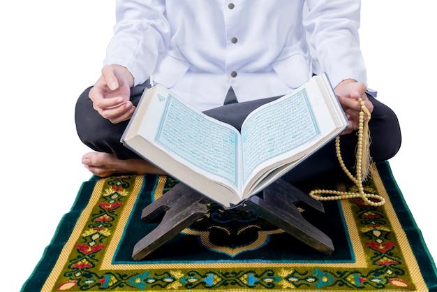 Vue rapprochée d'un homme musulman assis et priant avec des perles de prière
