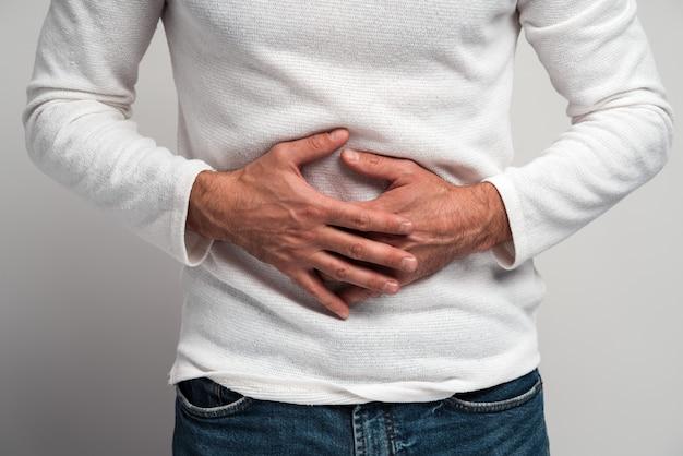 Vue rapprochée de l'homme tenant la main sur l'estomac ressentant une douleur aiguë, souffrant d'indigestion et de nausée, ulcère duodénal. studio intérieur tourné isolé sur fond blanc