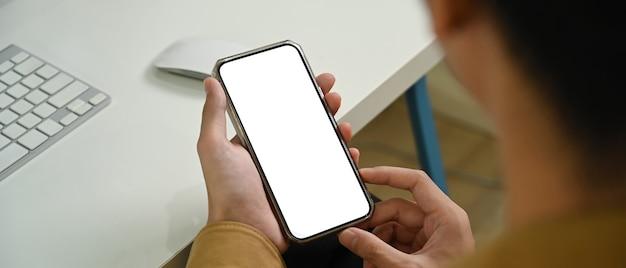 Vue rapprochée de l'homme tenant une maquette de téléphone intelligent avec écran blanc.