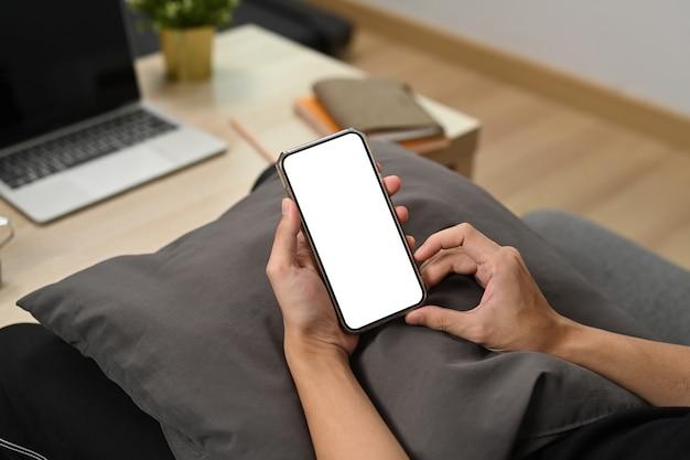 Vue rapprochée de l'homme tenant un téléphone intelligent alors qu'il était assis sur le canapé.