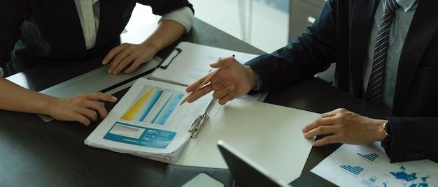Vue rapprochée des hommes d'affaires briefing sur leur projet avec des informations commerciales dans la salle de réunion