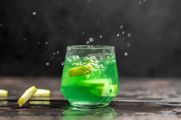 Vue rapprochée horizontale de jus de pomme dans un verre avec des citrons verts sur fond sombre