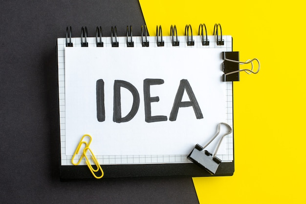 Vue rapprochée de l'idée avec feuille blanche sur cahier à spirale sur livre sur fond jaune noir avec espace libre