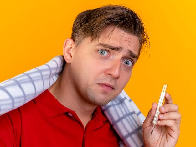 Vue rapprochée d'impressionné jeune bel homme malade blonde enveloppée dans un thermomètre à carreaux holding à l'avant isolé sur mur orange