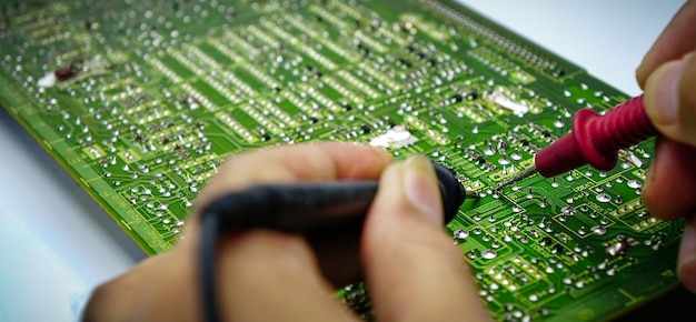 Vue rapprochée de l'ingénieur mâle testant la carte de circuit imprimé