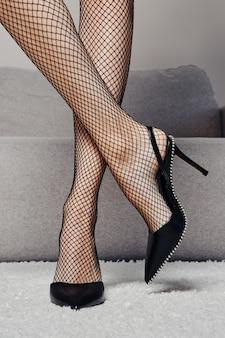 Vue rapprochée des jambes féminines minces dans des filets de pêche et des chaussures à talons hauts