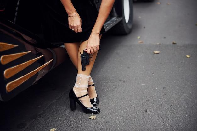 Vue rapprochée des jambes de la femme près de la vieille voiture. avec pistolet à la main.