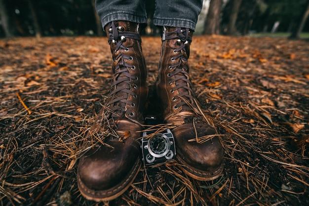 Vue rapprochée des jambes masculines en bottes de cuir vintage et montres en automne parc