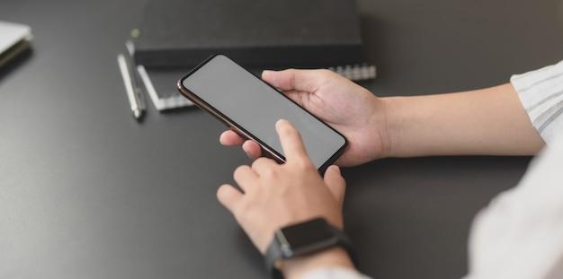 Vue rapprochée de la jeune femme d'affaires professionnel tenant un smartphone à écran blanc