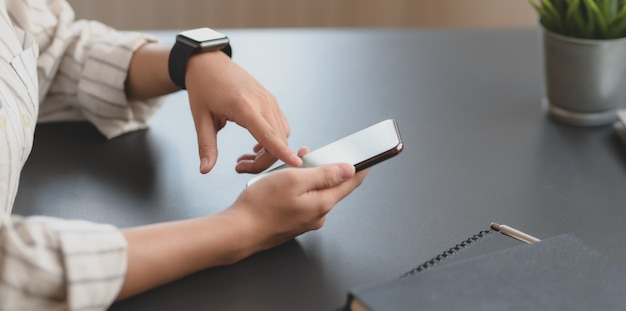 Vue rapprochée de la jeune femme d'affaires touchant le smartphone à écran blanc